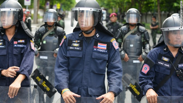 Thai police and army soldiers stand guard outside a military compound before former Prime Minister Yingluck Shinawatra arrives to report to Thailand's ruling military on May 23, 2014 in Bangkok, Thailand.T