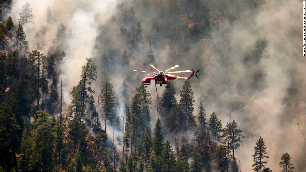 A helicopter helps battle the Slide Fire over Sterling Canyon in Sedona, Arizona, on Thursday, May 22. Hundreds of firefighters are battling high winds and steep terrain to contain the blaze.