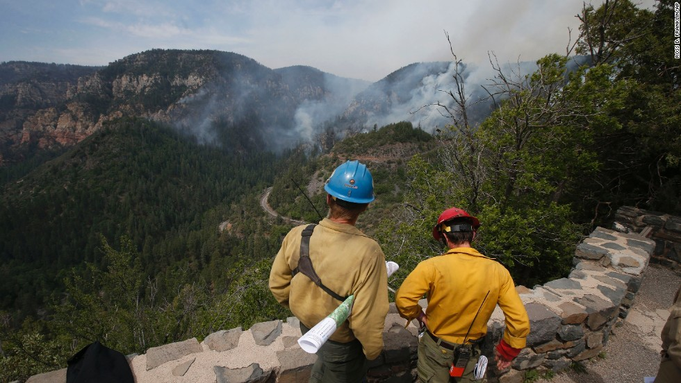 True Brown, left, of the Blue Ridge Hotshots, and Mark Adams of the Mormon Lake Hotshots take a high vantage point as spotters for those fighting a wildfire near Flagstaff, Arizona, on Friday, May 23. The fast-growing fire, dubbed the Slide Fire because it is just north of Slide Rock State Park, threatens several hundred homes and rental cabins in the area.