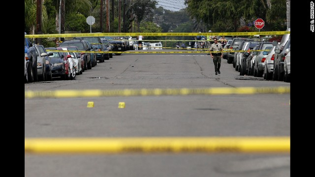 A Santa Barbara County deputy sheriff walks along the street on May 24 near the scene of the shooting in Isla Vista.