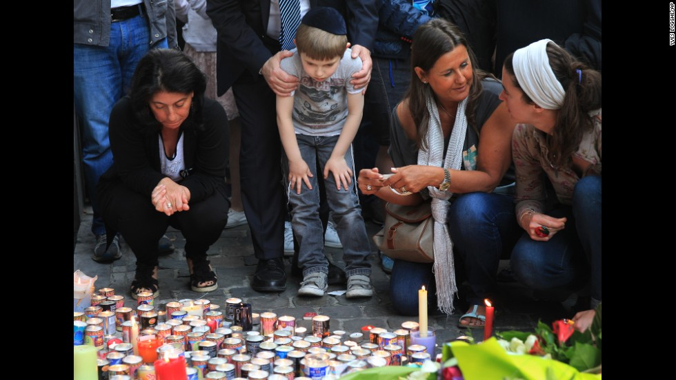 Three people were killed and a fourth was critically injured in the May 24 shooting. Here, people pay their respects Sunday, May 25, in front of a makeshift memorial at the entrance of the museum.