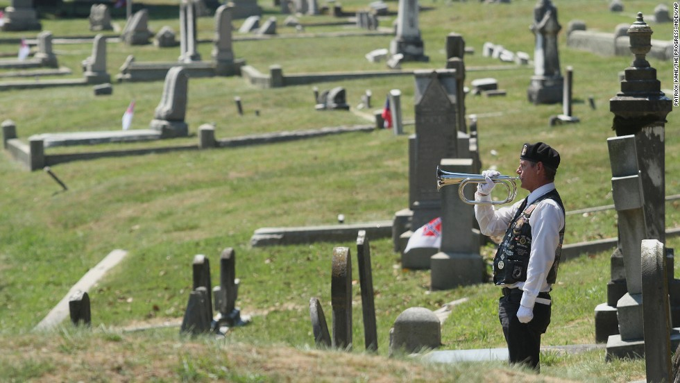 Robert Becker performs taps during a ceremony May 26, 2014, at Blandford Cemetery in Petersburg, Virginia.