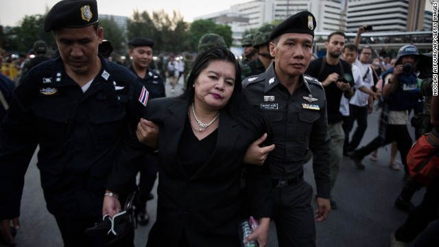 Thai police officers take a woman away from an anti-coup protest in Bangkok on May 26.