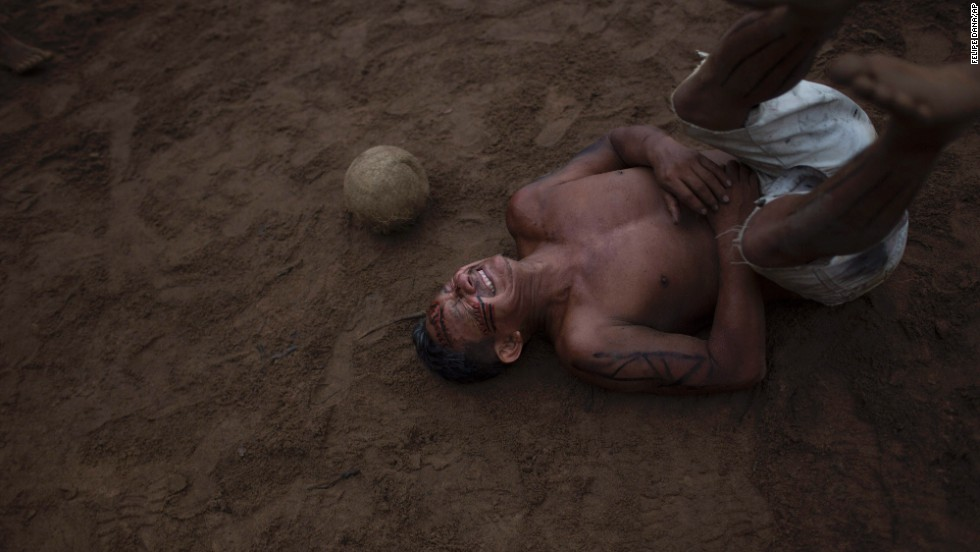 A man reacts Saturday, May 24, after being hit by the ball during a soccer game in the Tatuyo indigenous community near Manaus, Brazil. Manaus, in the Amazon rainforest, is one of the host cities for the upcoming FIFA World Cup.