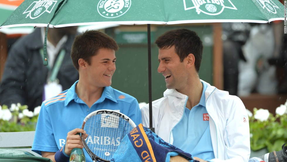 Novak Djokovic shares a moment with a ball boy during a break in play at the French Open in Paris. He went on to beat <br />Joao Sousa in straight sets in a match interrupted by the rain.