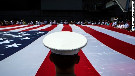 Members of the military unfurl an American flag during a wreath laying ceremony at the Intrepid Sea, Air & Space Museum in New York on Monday, May 26.