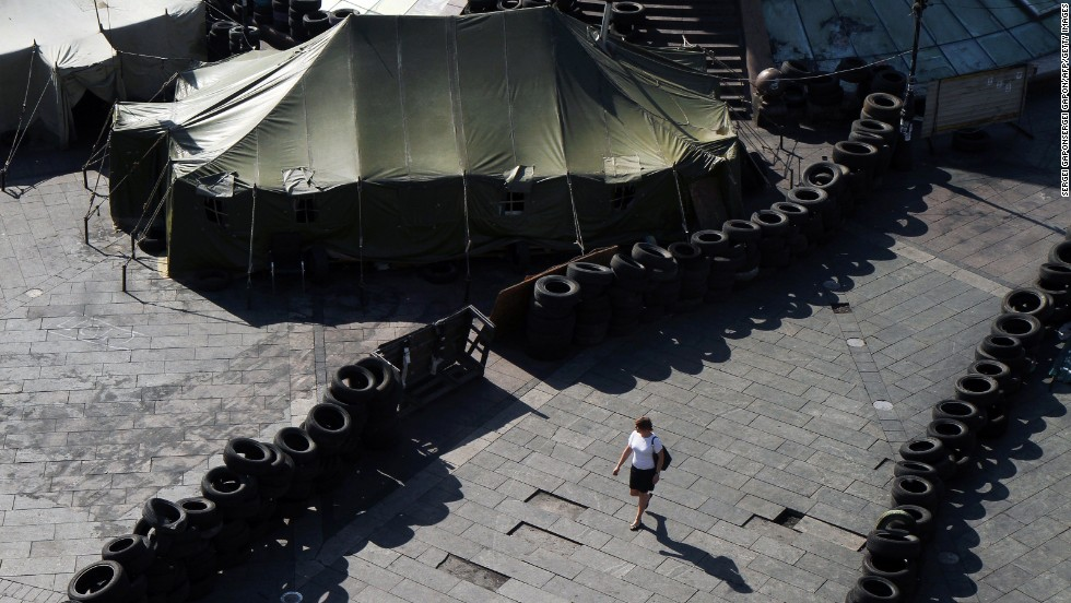 A woman walks May 26 near barricades built by protesters in Kiev's Independence Square. Vitali Klitschko, Kiev's future mayor and a former boxing champion, promised to dismantle the iconic protest encampment that helped oust Yanukovych but now clogs traffic and draws public complaints.