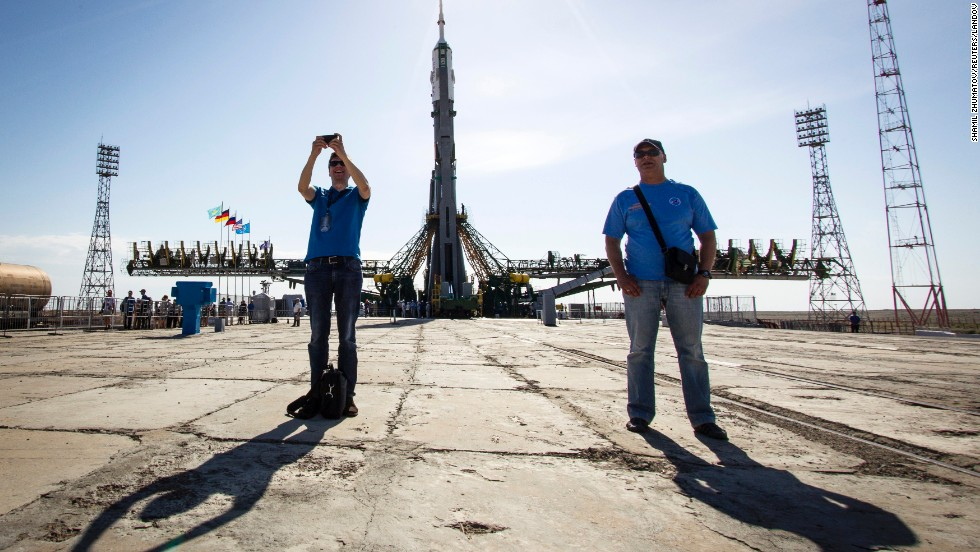 The Soyuz TMA-13M spacecraft is seen behind a man taking a selfie Monday, May 26, at the Baikonur Cosmodrome in Kazakhstan. The Soyuz is set to take three men to the International Space Station this week.