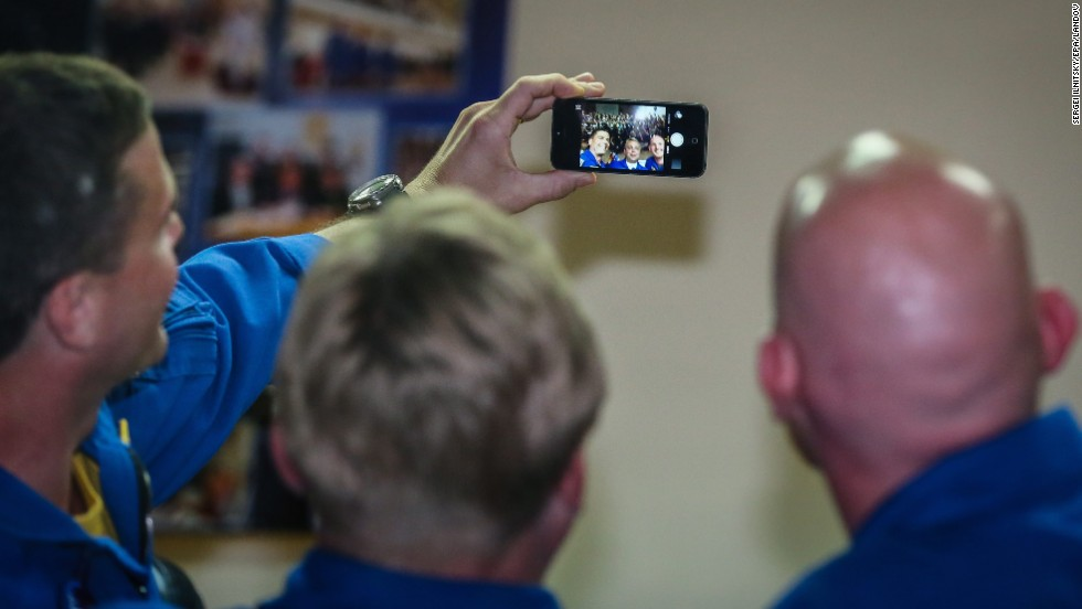 From left, Gregory R. Wiseman, Maxim Suraev and Alexander Gerst take a selfie on Tuesday, May 27, during a news conference at the Baikonur Cosmodrome in Kazakhstan. The men will be flying to the International Space Station this week.
