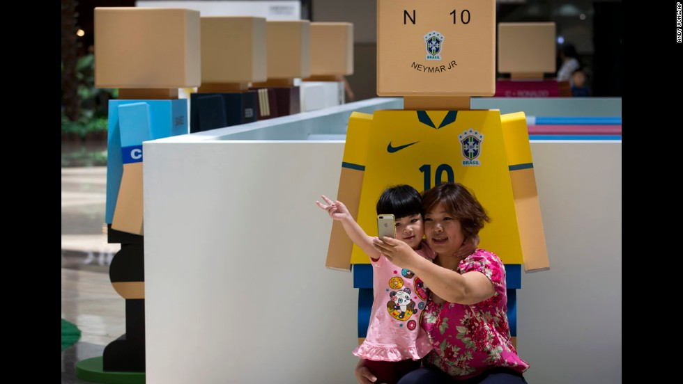 A woman and her child take a selfie in front of a figure symbolizing Brazilian soccer player Neymar at a shopping mall in Beijing on Sunday, May 25.