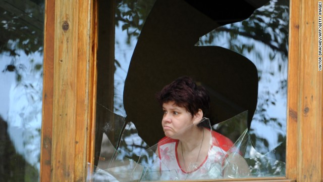 A woman looks out from a broken window in a bakery after a night of combat between pro-Russia separatists with Ukrainian troops in the eastern Ukrainian city of Slavyansk on May 27, 2014.