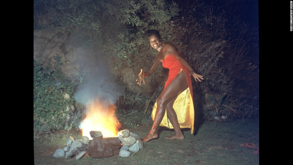 "Angelou was also a professor, singer and dancer whose work spanned several generations. Here, she dances next to a fire in this promotional portrait taken for the cover of her first album, ""Miss Calypso,"" in 1957."