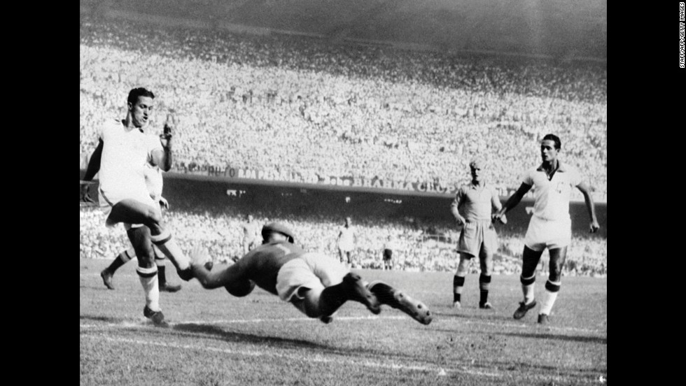Swedish goalkeeper Kalle Svensson dives to block the ball in front of Brazilian forward Ademir during a final-round match in Rio de Janeiro. Ademir, who scored four goals in the 7-1 thrashing, would go on to finish as the tournament's leading scorer with eight goals.