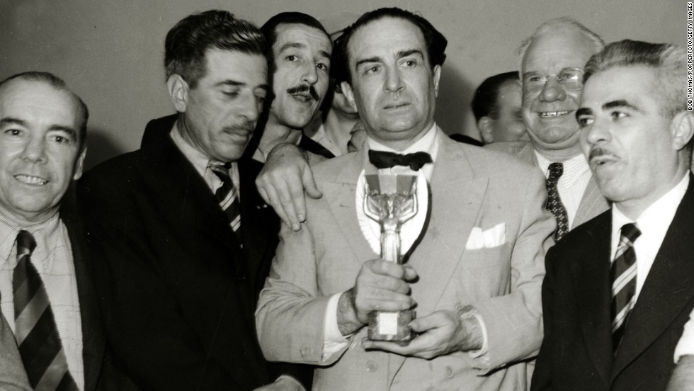 Uruguayan Ambassador Giordano Eccher, surrounded by team officials and journalists, holds the Jules Rimet Trophy, which is given to the World Cup winners.