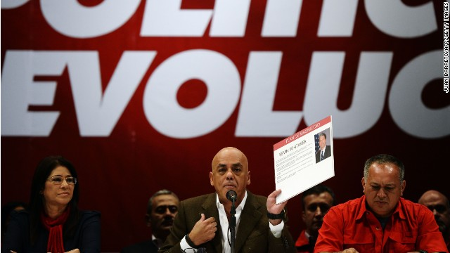 The mayor of the Libertador municipality Jorge Rodriguez (C) shows documents next to the President of National Emsembly Diosdado Cabello (R) and firts lady Cilia Flores during a press conference in Caracas on May 28, 2014. The leadership of Chavez Wednesday accused a handful of opposition politicians, including Congresswoman destitute Maria Corina Machado and the US ambassador in Colombia, Kevin Whitaker, of plotting a coup and assassination against the president Nicolas Maduro.