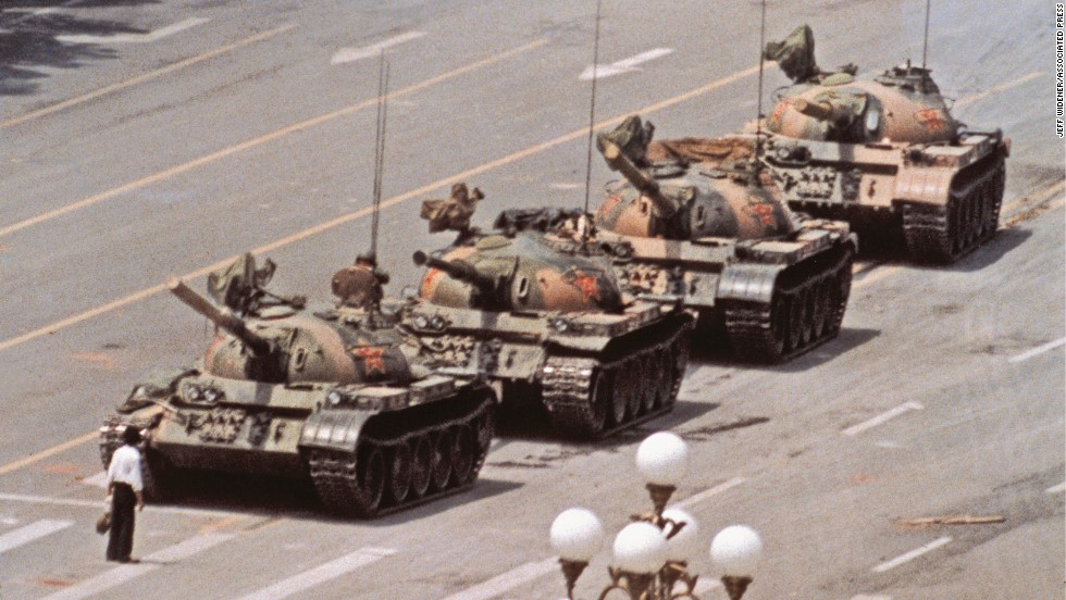 "June 5, 1989, Tiananmen Square: A day after the military opened fire on protestors, photographer Jeff Widener was setting up the shot for the now iconic ""tank man"" image: ""I was leaning over the balcony aiming at this row of tanks, and the guy walks out with this shopping bag and I was thinking 'the guy is going to ruin my composition.'"" The final photo won the Scoop Award in France, the Chia Sardina Award in Italy, and was a finalist for the Pulitzer Prize."