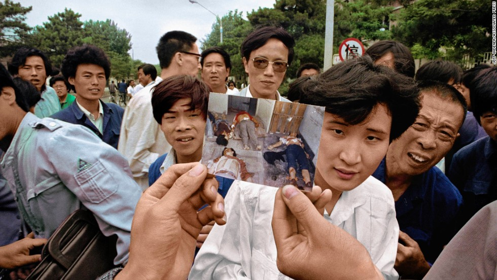 "June 5, 1989, and people on Chang'an Avenue show a picture of the bodies of protestors at a morgue. Commemoration of the martyrs is not allowed in China, except for in Hong Kong. Widener is currently in the city for the 25th anniversary. ""This year although they would allow me back into mainland China, I did think it would be a little too intense. I am here in Hong Kong because it just seemed like the right place to be for me personally. I want to photograph the commemorations in Hong Kong as a continuation of the tank story."