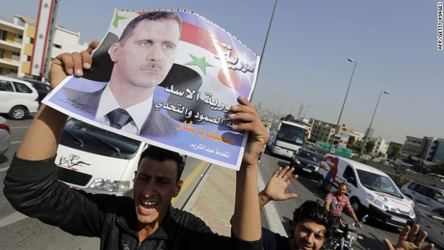 Syrian expatriates living in Lebanon carry a poster of Syrian president Bashar al-Assad, as they arrive to cast their ballots in their country's presidential elections, outside the Syrian Embassy in Yarze east of Beirut on May 28, 2014. Filling the streets around the embassy in Beirut, thousands of Syrians turned out to vote in a controversial presidential election that Bashar al-Assad is expected to clinch effortlessly, as civil war rages. AFP PHOTO/ JOSEPH EIDJOSEPH EID/AFP/Getty Images