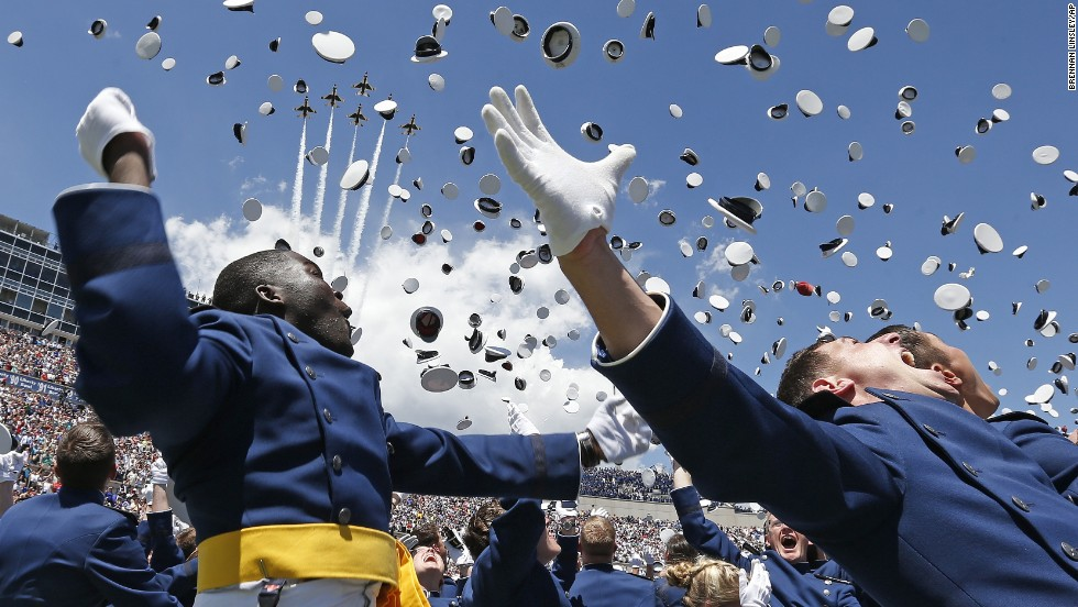U.S. Air Force Academy graduates throw their caps into the air Wednesday, May 28, as jets fly over the stadium in Colorado Springs, Colorado.