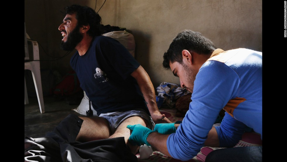 "Ahmad al-Jarak treats the wounds of Mohammad Houweija in the countryside near Idlib, Syria, on Monday, May 26. Houweija was shot in the thigh during clashes in the village of Saraqib. <a href=""http://www.cnn.com/2014/02/10/middleeast/gallery/syria-unrest-2014/index.html"">See more photos from the Syrian civil war</a>"