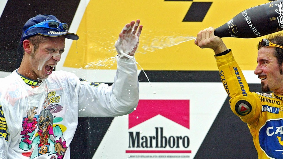 Rossi is on the receiving end of the champagne as compatriot Max Biaggi toasts him after wrapping up a third straight world title in Malaysia in 2003.