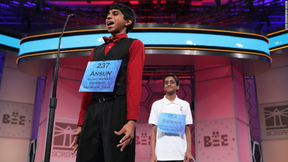 "Hathwar, right, looks on as Sujoe correctly spells ""feuilleton"" in the bee's final round. Hathwar correctly spelled the word ""stichomythia."""