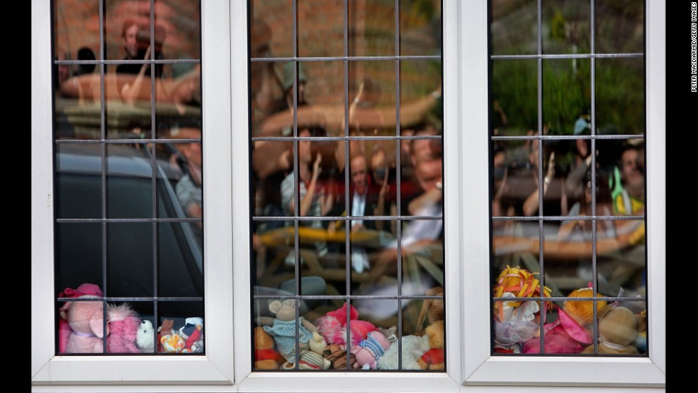 Reporters and television crews are reflected in the playroom window of the McCann family home in Rothley, England, in September 2007.