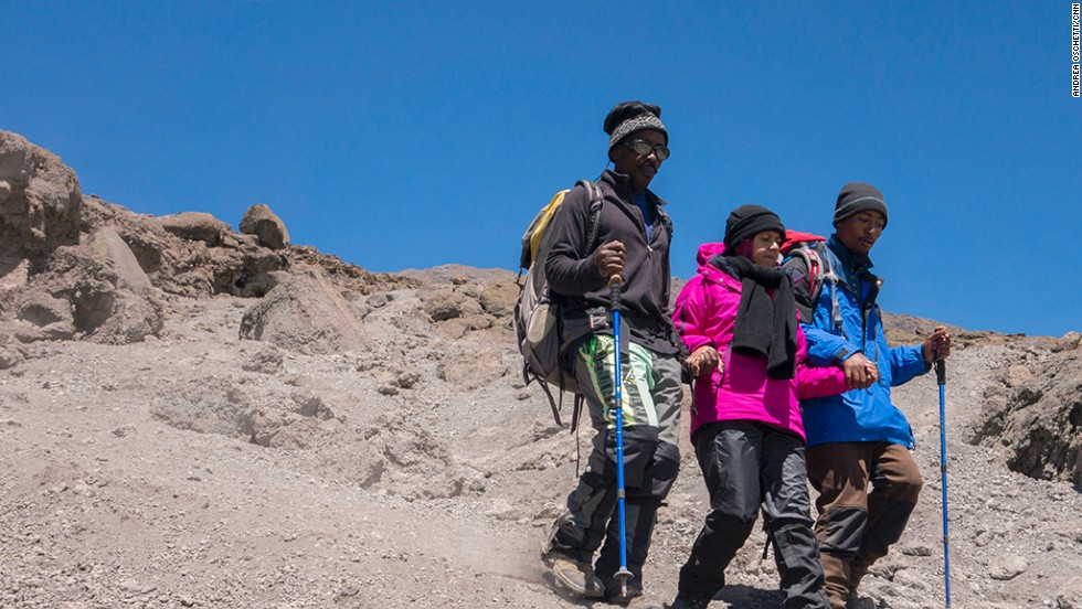 Some climbers suffer from altitude sickness or exhaustion and have to be supported down the mountain, hand in hand, by their guides.