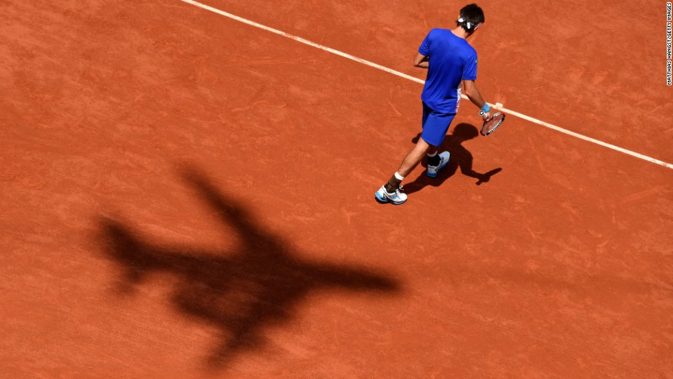 An airplane's shadow is seen on the red clay of Roland Garros as tennis player Leonardo Mayer walks to the service line Saturday, May 31, in Paris. Mayer was playing Rafael Nadal, who he lost to in the third round of the French Open.