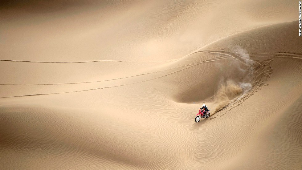 Wang Yirong rides his motorcycle through a desert in China's Xinjiang Uyghur Autonomous Region as he competes in the China Taklimakan Rally on Saturday, May 31.