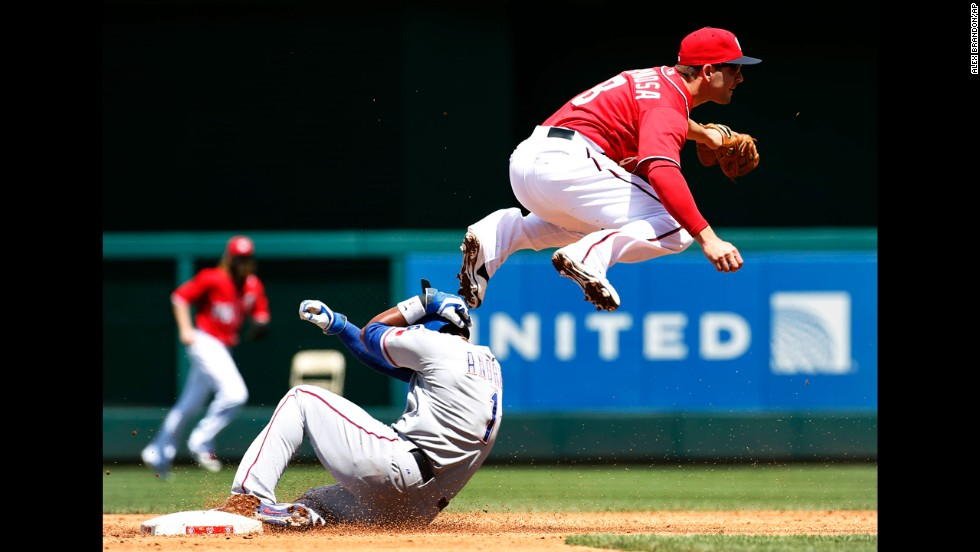 Washington Nationals second baseman Danny Espinosa jumps over Elvis Andrus of the Texas Rangers as he turns a double play during an interleague baseball game Sunday, June 1, in Washington. The Rangers won 2-0 to avoid a three-game sweep.