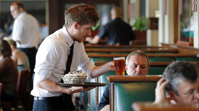 Waiter Spencer Meline serves a customer at Ivar's Acres of Clams restaurant on the Seattle waterfront Wednesday, May 14, 2014. While the Seattle mayor is proposing to raise the minimum wage to $15 in the coming years to the highest level in the nation, some activists say that's too slow and are threatening to take the issue to voters with a ballot measure that would force a raise sooner. As the mayor's plan is being debated by the council, businesses are sounding the alarm that raising the wage too quickly could hurt their revenue and force them to either hire fewer workers or let go more of their employees, while popular restaurateurs have emphatically argued for counting tips in total compensation. (AP Photo/)