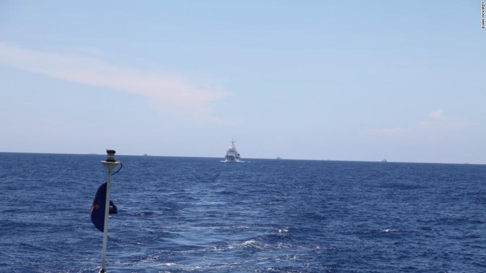 A Chinese Coast Guard vessel follows CG 8003 at a discreet distance.