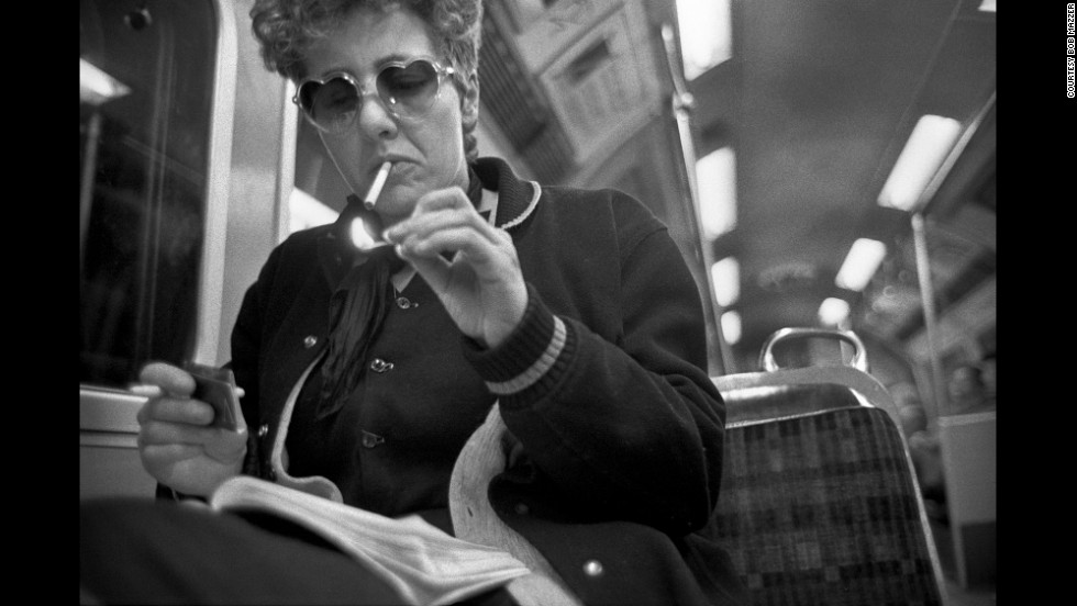 "Smoking on the tube was commonplace when Mazzer started his project. Here, a woman in heart-shaped ""Lolita"" glasses lights up in the early 1980s."