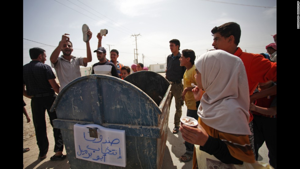 "Syrian refugees at the Zaatari camp in Jordan put their shoes in a trash bin that reads ""voting box"" during a protest against the election on June 3."
