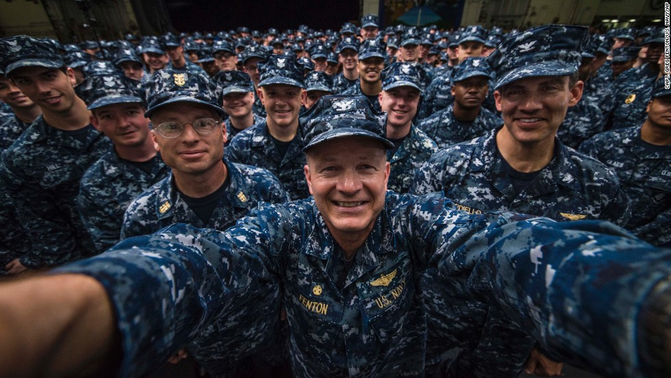 U.S. Navy Capt. Greg Fenton, commanding officer of the USS George Washington, takes a photo in the aircraft carrier's hangar bay after a promotion ceremony Friday, May 30, for 275 sailors behind him.