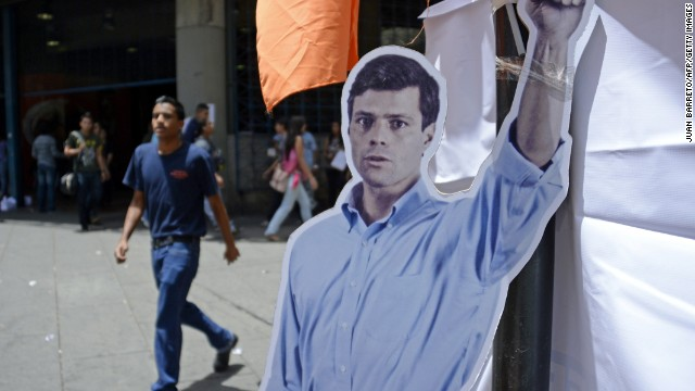 People walk pass next to a poster with the silhouette of arrested opposition leader Leopoldo Lopez in Caracas on June 02, 2014. Lopez, on remand jail for more than 100 days ago appears on Monday for the second time at the Venezuelan Supreme Court that could sentence him to 10 years in prison on charges of conspiracy, arson and property damage.