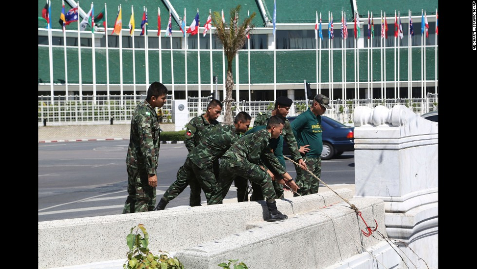 Soldiers pull barbed wire from a canal near the Thai Government House during a cleanup operation June 4 in Bangkok.