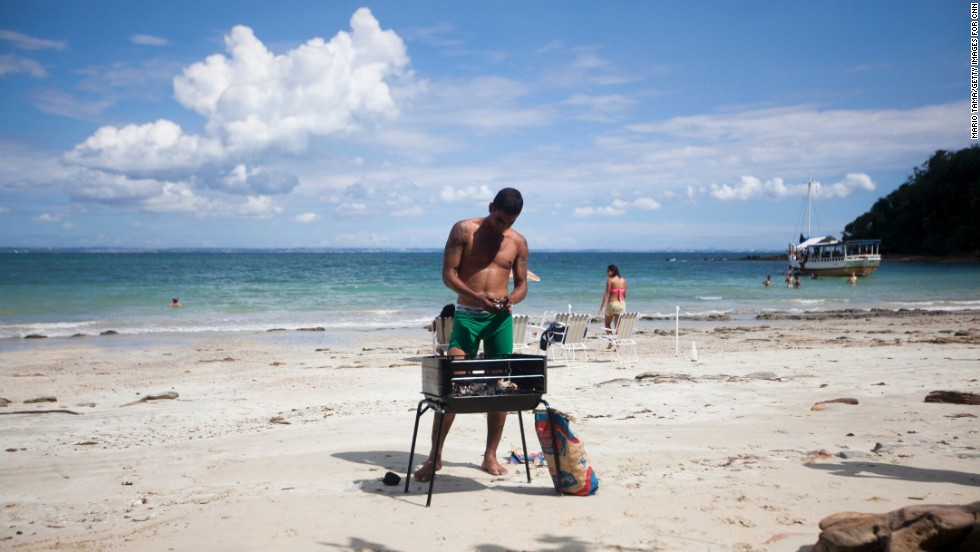 A man sets up a grill on the beach in Bahia. Seafood is a staple of the local cuisine.