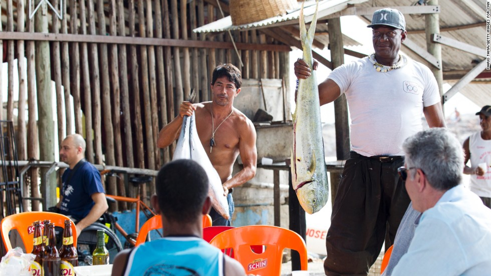 Bourdain, bottom right, relaxes with fishermen after a long day on the water.