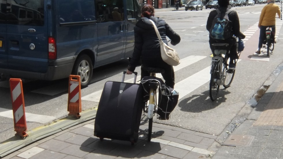 Why use the train to carry your suitcase the full 20 kilometers to Amsterdam's airport when you can cycle?