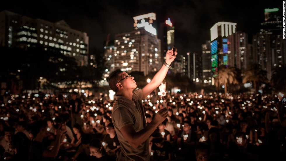 A man in Hong Kong takes a picture with his cell phone as people hold up candles Wednesday, June 4, to commemorate the 25th anniversary of the Tiananmen Square crackdown in China. In 1989, after several weeks of demonstrations, Chinese troops entered Beijing's Tiananmen Square and fired on civilians.
