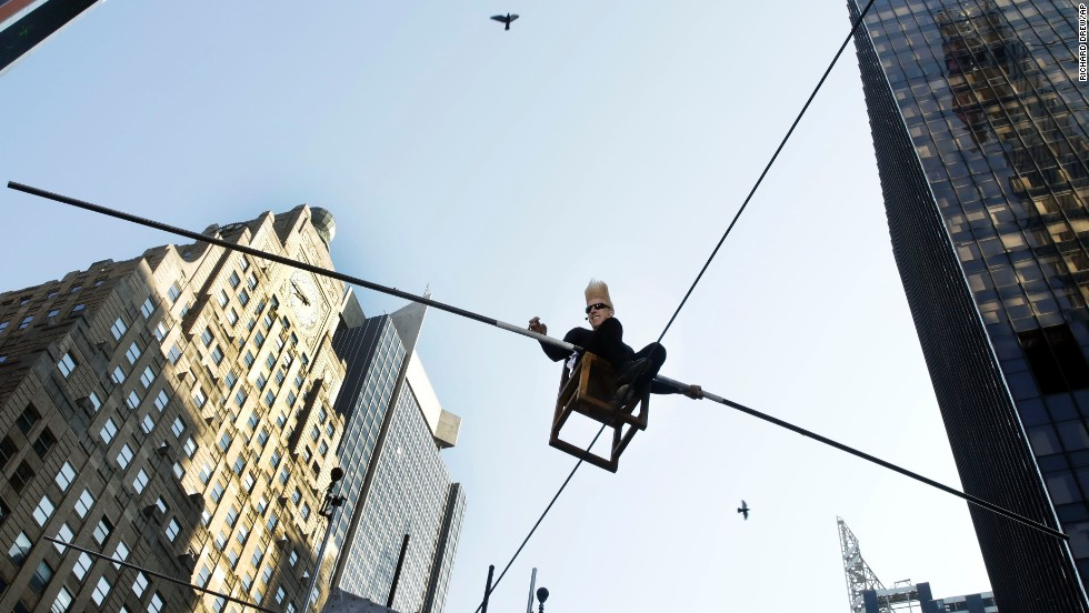 Bello Nock, a seventh-generation circus performer, sits on a chair 27 feet above New York's Times Square on Tuesday, June 3, as he sets an unusual record -- balancing on a wire while giving eight hours of continuous interviews.