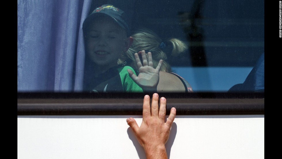 "A boy waves to a relative Thursday, June 5, as he boards a bus in Luhansk, Ukraine, to leave to a safer region. Pro-Russian separatists <a href=""http://www.cnn.com/2014/05/27/world/gallery/ukraine-after-election/index.html"">continue to battle Ukrainian troops</a> in the country's east."