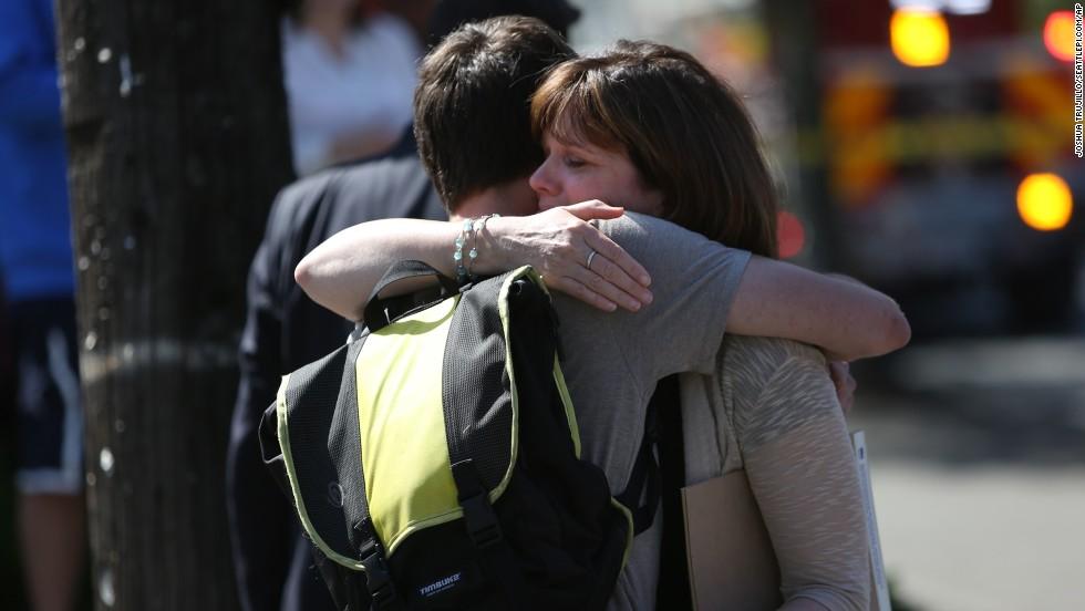 Bystanders embrace near the scene.
