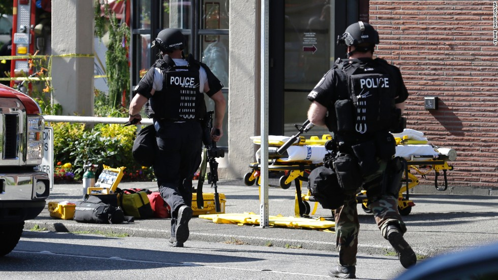 Seattle police officers run toward a campus building after the shooting June 5.