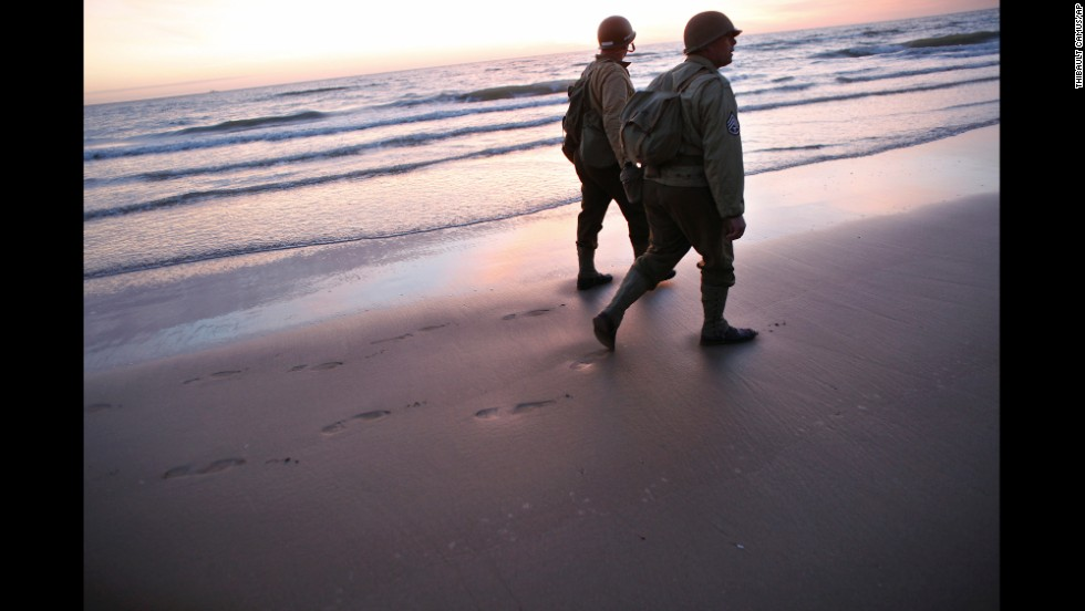 World War II reenactors walk along Omaha Beach near Vierville-sur-Mer, France, on Friday, June 6, the 70th anniversary of D-Day.