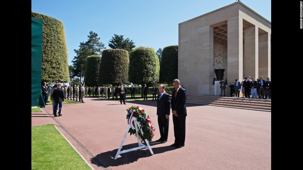 President Barack Obama and French President Francois Hollande pause for a moment of silence after laying a wreath at the Normandy American Cemetery in Colleville-sur-Mer, France, on Friday, June 6, the 70th anniversary of D-Day. Obama's travel agenda also includes Poland and Belgium.