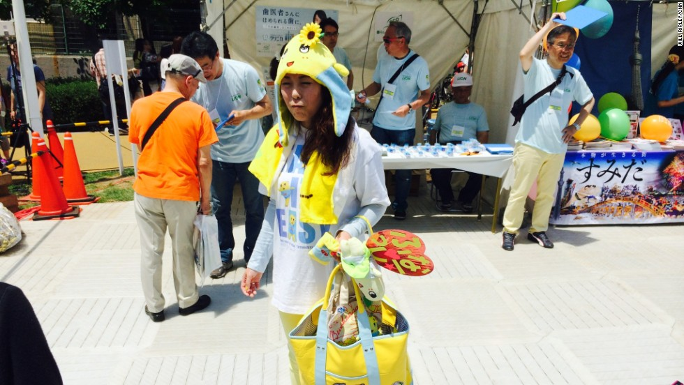 Tokyo resident Mika Asano, 32, poses with some of her Funassyi merchandise, which she estimates cost her more than $1,000. Mascots appeal to people of all ages in Japan, with many adult fans.