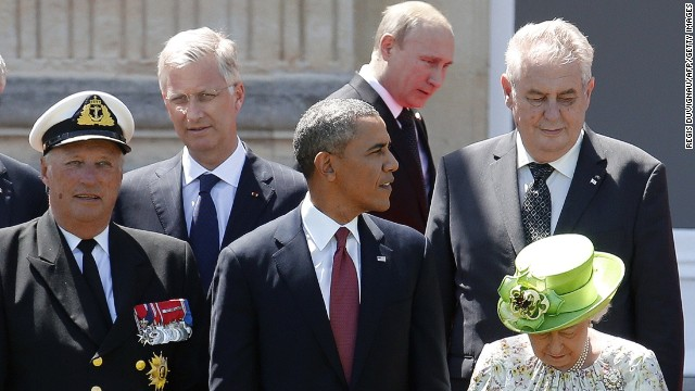 Russian President Vladimir Putin (C top) passes behind US President Barack Obama (C), Britain's Queen Elizabeth (bottom R), Norway's King Harald (L) and King Philippe of Belgium (L top) as he arrives for a group photo for the 70th anniversary of the D-Day landings at Benouville Castle, June 6, 2014.